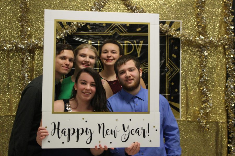 Seniors Bryce Cole, Alexis Griman, Ashlynn Hooper, Clarissa Gray, and Demitri Hines pose with the photo booth props at the Winter Dance on Fri. Jan. 18. The theme, Cheers to the New Year!, gave students an opportunity to celebrate the start of 2019 together.