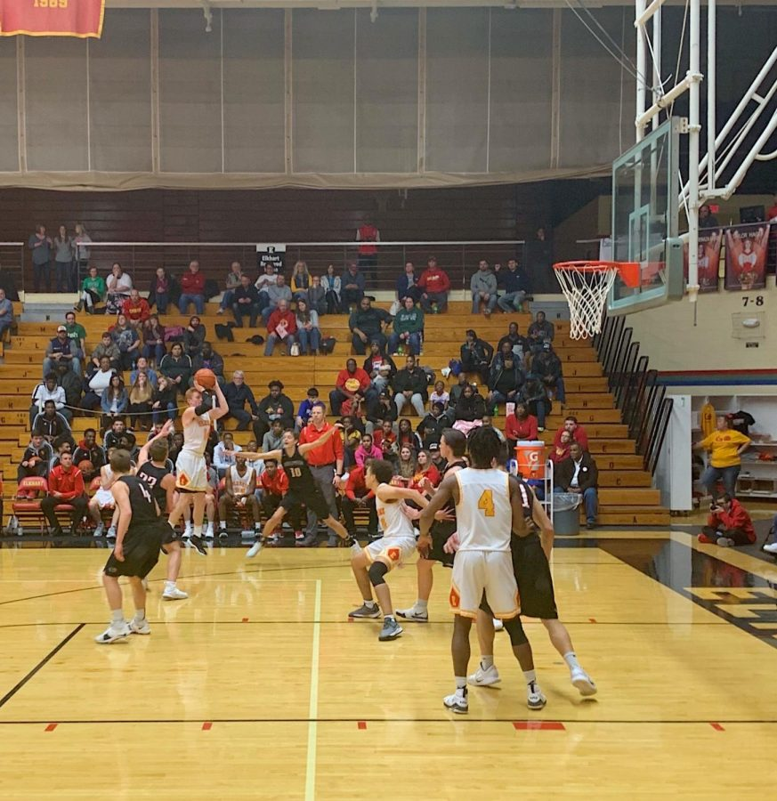 Senior Hank Smith rises up for a three point shot over two Panther defenders.