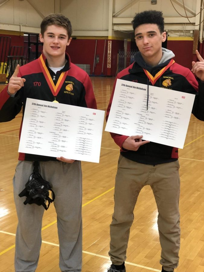 Sophomore Clayton Lundy and junior Kamden Goering hold up their bracket, for the 37th Annual Jim Nicholson tournament held in the Elkhart Memorial Fieldhouse on Saturday Dec. 8. 2018. Lundy and Goering won first in their weight class.