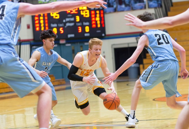 Senior Hank Smith dribbles through two St. Joe defenders. The Indians defeated the Chargers in a close game, 63-62
