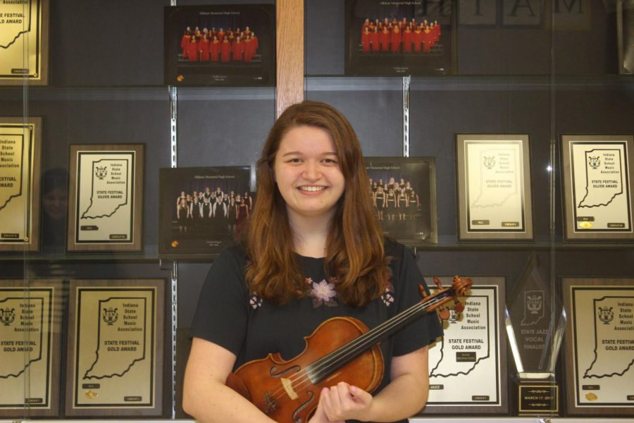 Junior Anna-Mariah Jacobo poses with her violin in front of the orchestra trophy case on Thursday, Feb. 28. Jacobo is our GENESIS Musician of the Week.