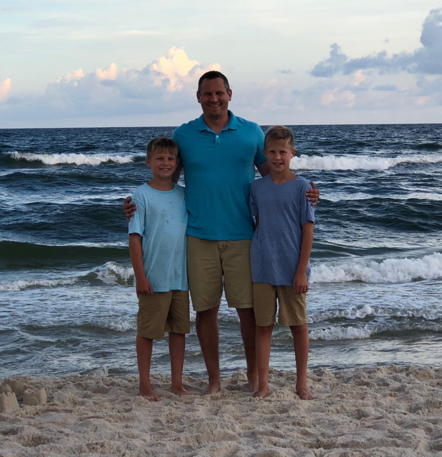 Todd Sheely stands with his two sons, Brennan (left) and Mayson (right), in Gulf Shores, Alabama. Sheely was named the Elkhart Memorial 2019 Teacher of the Year.