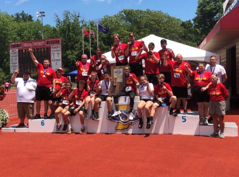 Sheely stands alongside the 2018 State Champion Unified Track team at Indiana University shortly after receiving their trophy. Coach Sheely led the team to Elkhart Memorial's very first state championship.