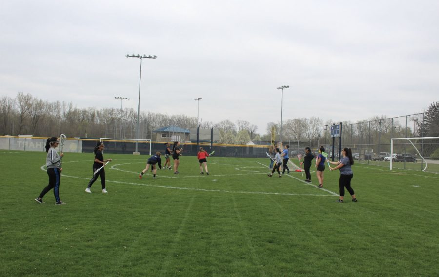 The girls lacrosse team completes a passing drill during the beginning of practice at the Central soccer field on Thursday, April 25.