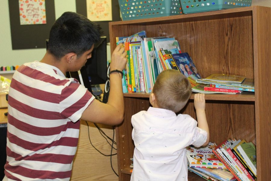 Freshman Santos Dimenez and his preschool buddy pick out a book to read together on Wednesday, April 17. The EMHS Preschool ran by teacher Kara Sears and Advanced Child Development is a way for high schoolers to gain first hand experience with children.