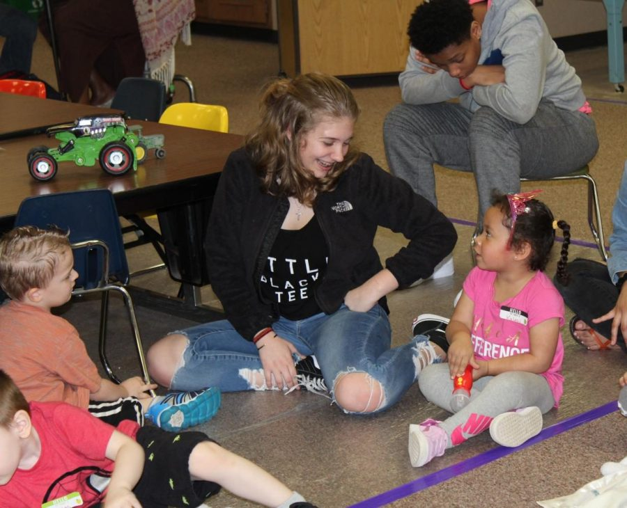 Freshman Brianna Huss smiles as her preschool buddy talks about a microphone she brought for