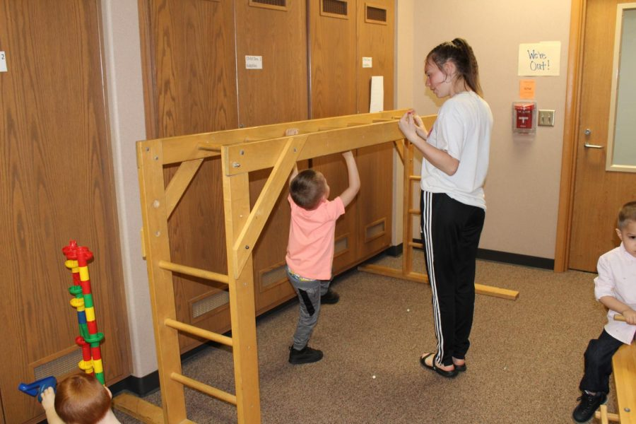 Sophomore Gabrielle Moore teaches her preschool buddy how to go along the monkey bars on Wednesday, April 17. The EMHS Preschool ran by teacher Kara Sears and Advanced Child Development is a way for high schoolers to gain first hand experience with children.