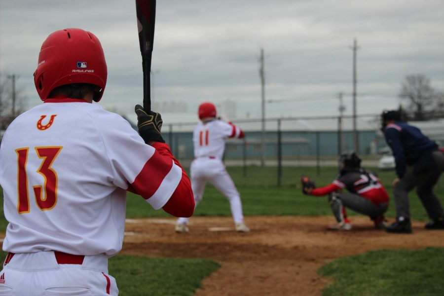 Sophomore Dylan Rost (11) waits for the pitch during the Chargers game against Goshen High School on Friday, April 19 while sophomore Graham Elli is on deck timing up his swing.