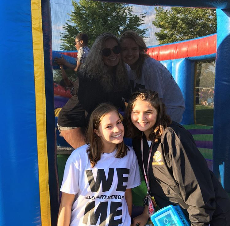 Seniors Kaitlin Presswood and Megan Huys along with Juniors Emily Anderson and Felisha Campanello smile for a picture at the City Wide Pep Rally on Aug. 24. The four girls helped the community by working the jousting bounce house for the kids.