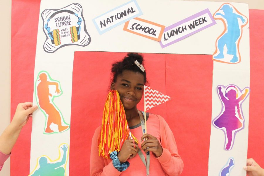 Samaria Henderson Poses in front of the National School Lunch Week during lunch on Friday, Oct. 18.
