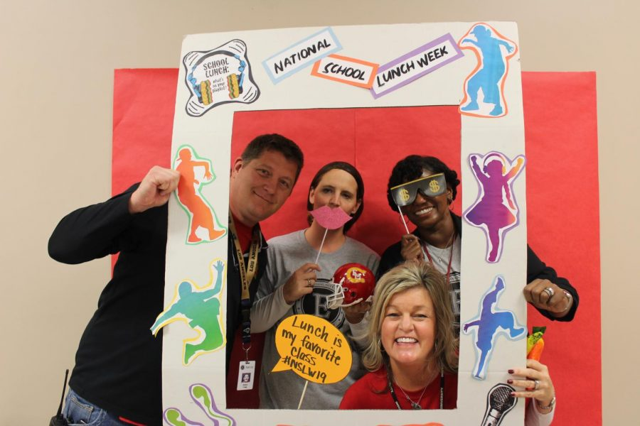 Denny Trigg, Julie Tyrakowski, Latosha Bonds, and Stephanine Doncilovic pose with props in the National School Lunch Week frame on Friday, Oct. 18.