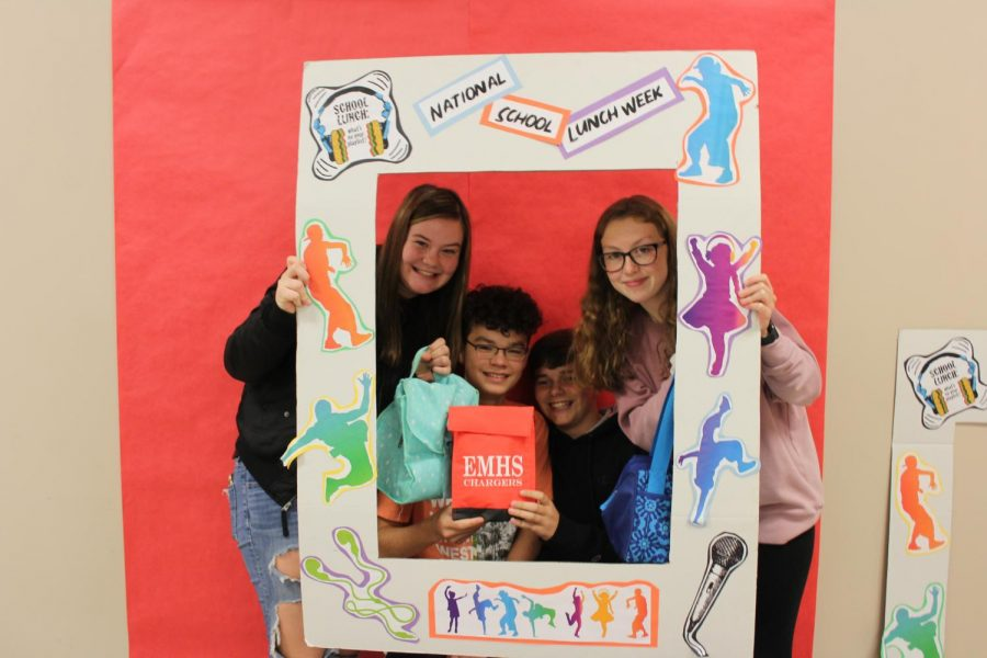 Freshmen Abigail Presswood, Ethan Swank, Sam Brown, and Riley Wolschlager hold up props for the National School Lunch Week photo booth that was held during Friday, Oct. 18.
