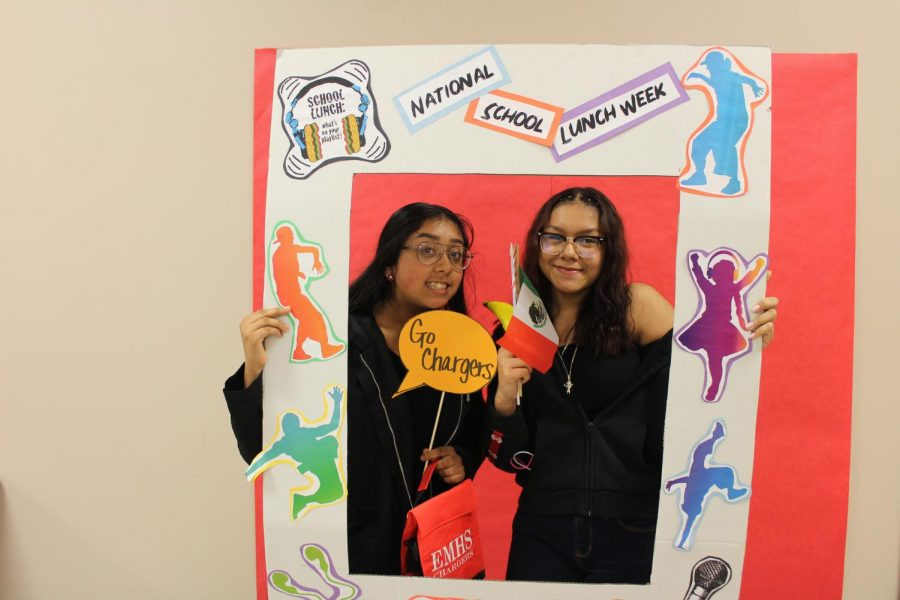 Sophomore Wendy Sierra Garcia and Leslie Murillo-Leon pose behind the National School Lunch Week frame during lunch on Friday, Oct. 18.
