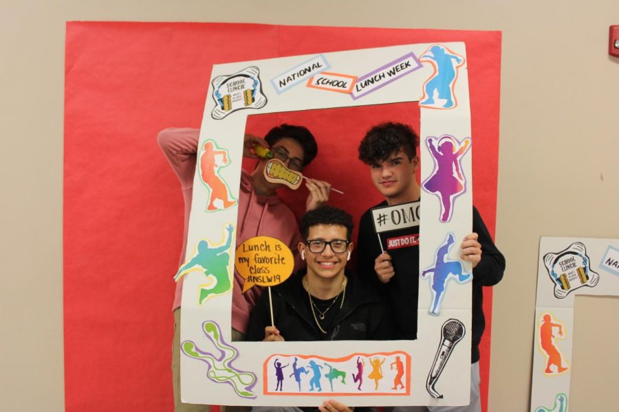 Alexander Lefever (11), Esvin Herrera (12), and Tyler Hostetter (12) take time during lunch to pose with the National School Lunch Week frame on Friday, Oct. 18.
