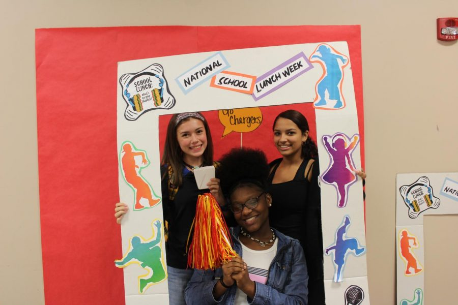 Sophomores Jenna Copsey, Aja Hall, and Kyiah Onyon hold up the National Lunch Week frame during lunch on Friday, Oct. 18.