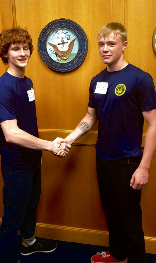 Seniors Chance Shank and Garrett Culp shake hands in front of the Navy crest on Friday, Oct. 11. The friends will be attending boot camp this summer.