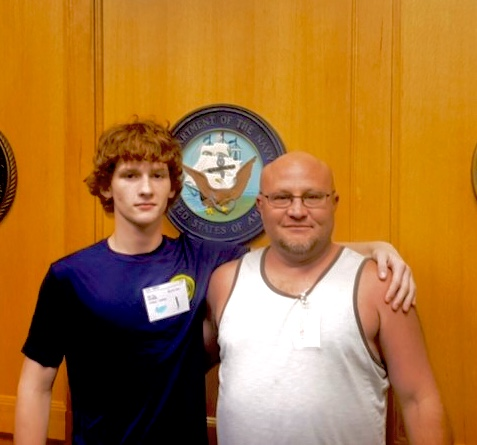 Senior Chance Shank and his father pose for a picture in front of the US Navy crest on October 11. Chance's family is very supportive and excited about his admission into the military.