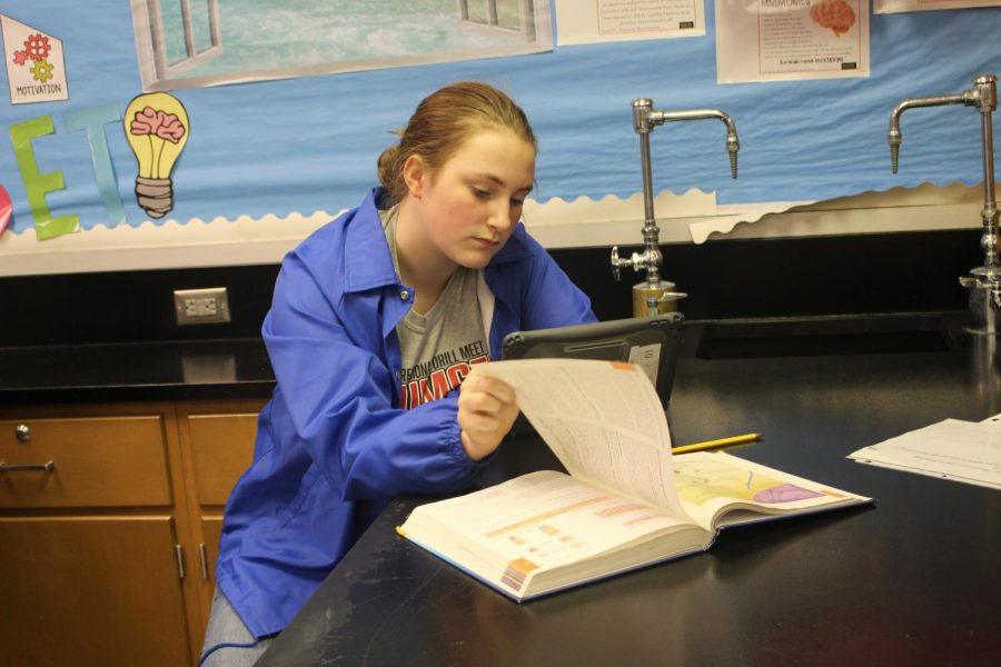 Before moving on to the next lab, Junior Valerie Cole opens her book to study the parts of the epithelium tissue on Monday, Nov. 4.