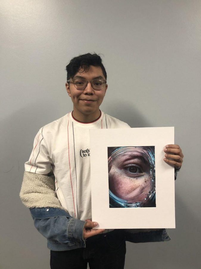 On Friday, Nov. 22, Senior Mario Castro holds a photograph that he took which is on display in the new Arts and Communication hub.