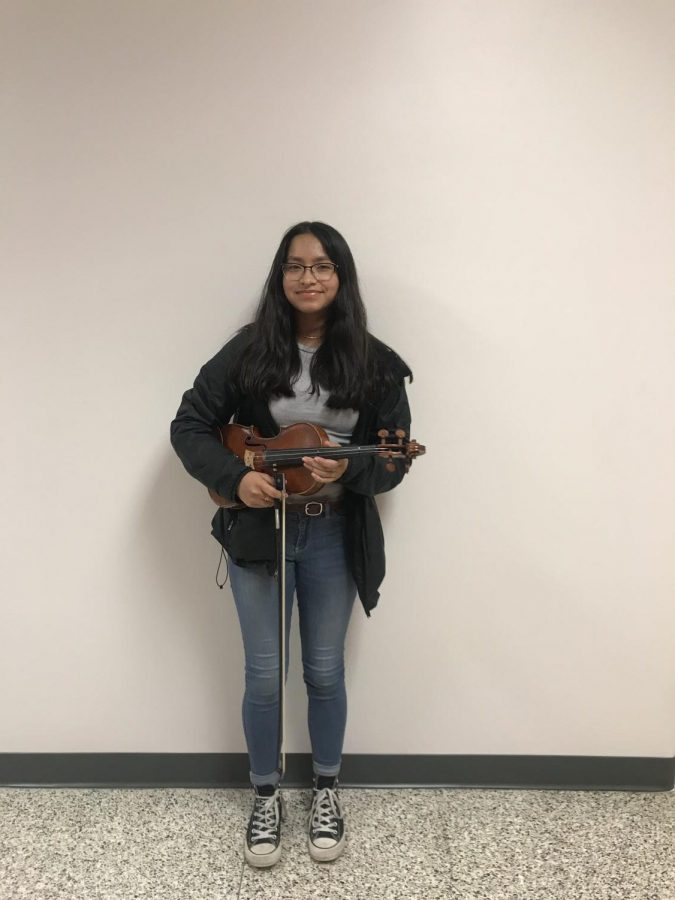Junior Celeste Ramirez poses with her violin which she's been playing for five years.