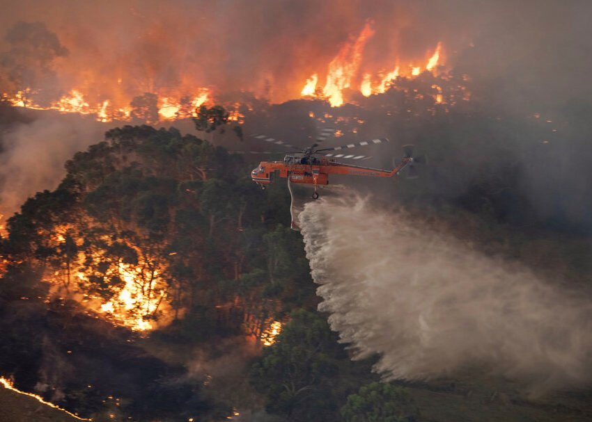 In this Monday, Dec. 30, 2019 photo provided by State Government of Victoria, a helicopter tackles a wildfire in East Gippsland, Victoria state, Australia. Wildfires burning across Australia's two most-populous states trapped residents of a seaside town in apocalyptic conditions Tuesday, Dec. 31, and were feared to have destroyed many properties and caused fatalities. (State Government of Victoria via AP) https://creativecommons.org/licenses/by/2.0/