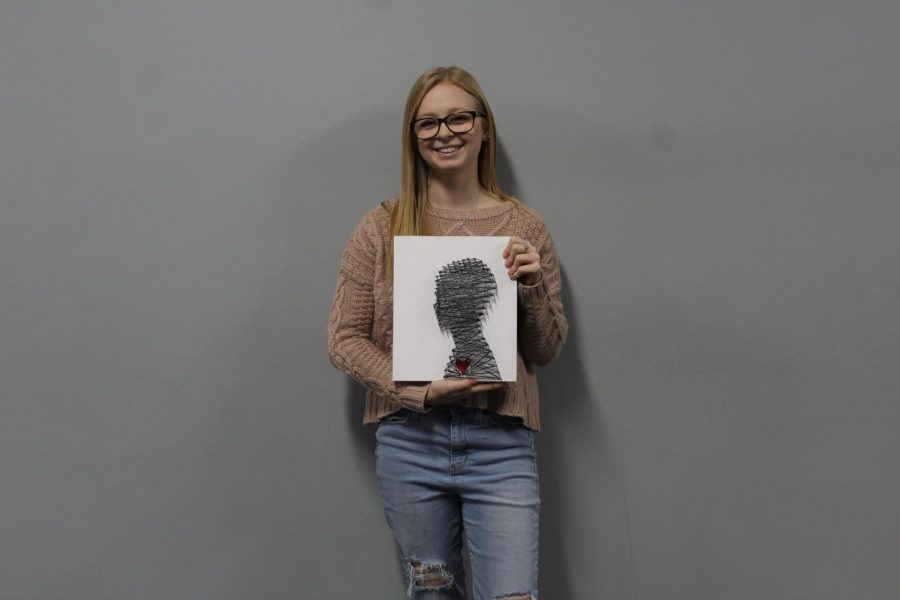 Junior Chloe Sharp posing with one of her artworks entitled