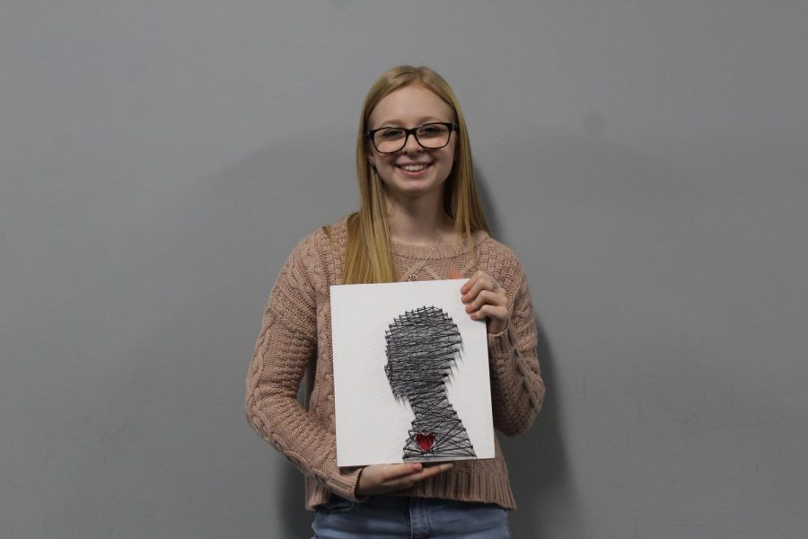 Junior Chloe Sharp poses with a piece of her work entitled