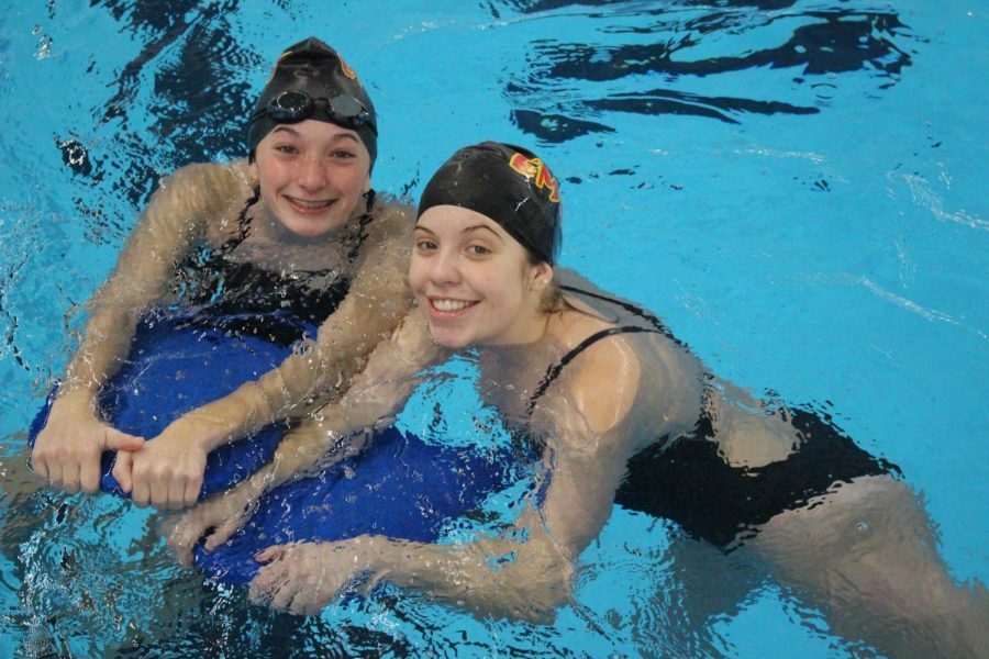 Sophomore Kailey Gregg and Junior Gabby Scott smile during warm-ups at the Elkhart Aquatic Center on Thurs. Jan. 2. The girls used floating devices as tools to warm-up their legs.