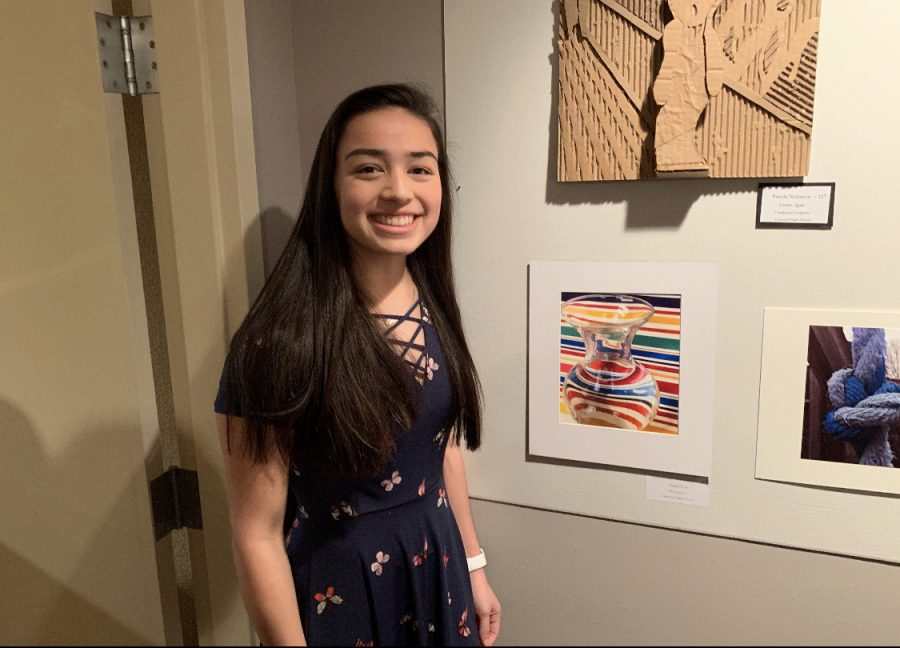 Huys stands beside beside her photograph in the South Bend Museum of Art in February 2019.