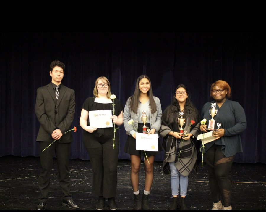 Oratory winners line up on stage after the competition. Fifth place Kainoa Harada (10), fourth place Isabella Lull (12), Third place Jahlea Douglas (12), second place Daniela Morales (11), and first place Shamaya Bell (12)