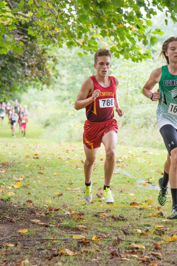 Sophomore Teagan Rodriguez works to pass a Concord runner during the 2019 cross country season. He is our GENESIS athlete of the week.