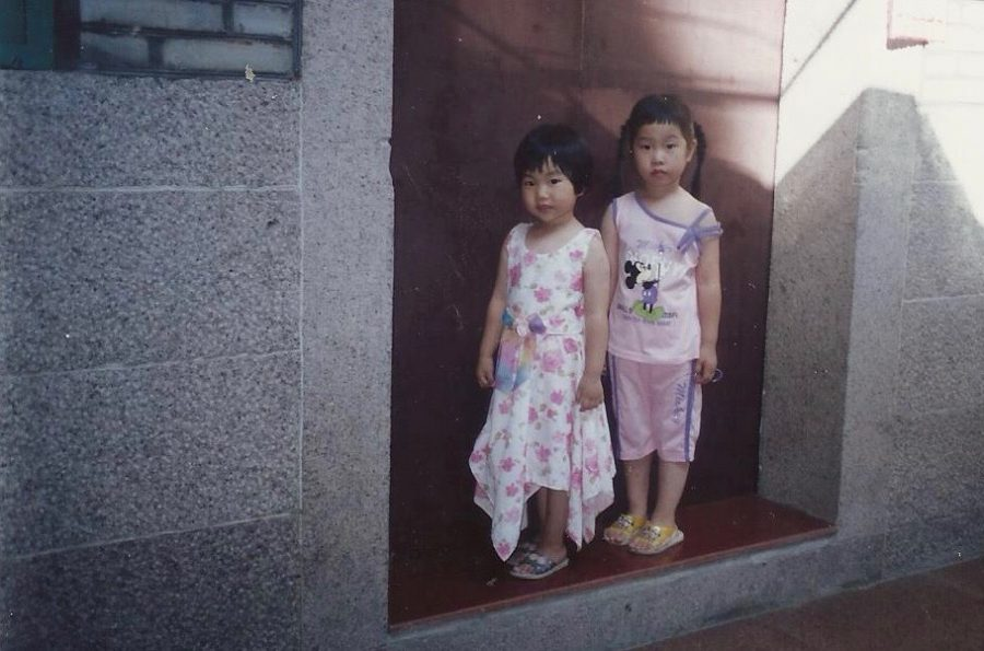 Junior Jamie Zheng (left) and her sister, senior Jenny Zheng (right) pose together in their hometown of Fuijian, China.