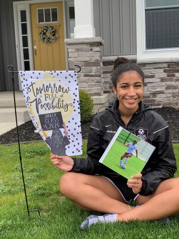 Senior, Jahlea Douglas, poses with her photo book and senior flag purchased by her adopted senior. Adopt a senior is a facebook group that many schools have created to recognize seniors.